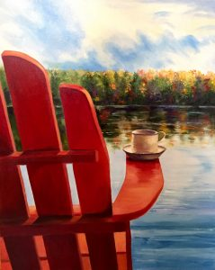 Adirondack chair facing the water, with a cup balanced on its arm.