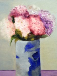 Pink and Blue flowers in a blue and white vase.
